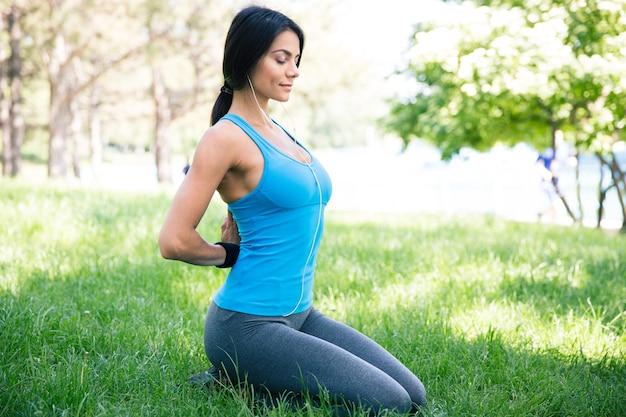 緑の芝生で瞑想するフィットネス女性