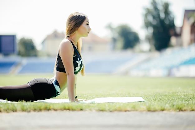 Фитнес женщина на стадионе настила на зеленой траве