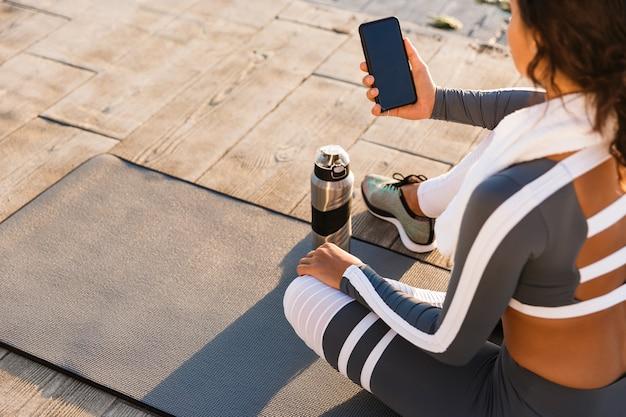 Фитнес женщина на открытом воздухе с помощью мобильного телефона