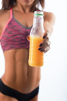 Fitness woman posing with a bottle of juice
