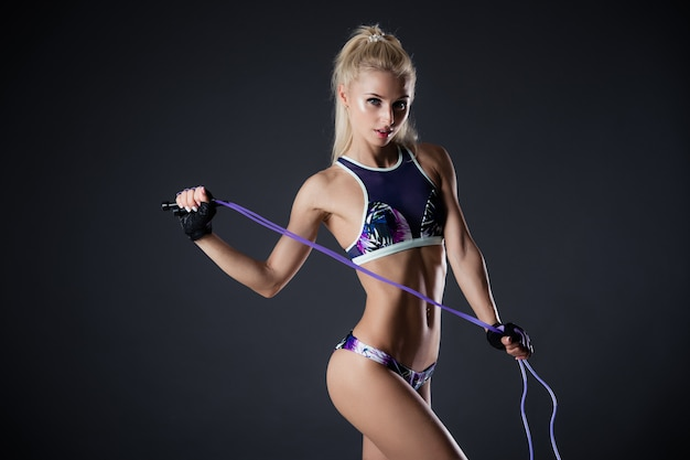 Fitness woman posing with skipping rope on a black background. sports motivation. perfect female fit figure. sexy girl in the studio.