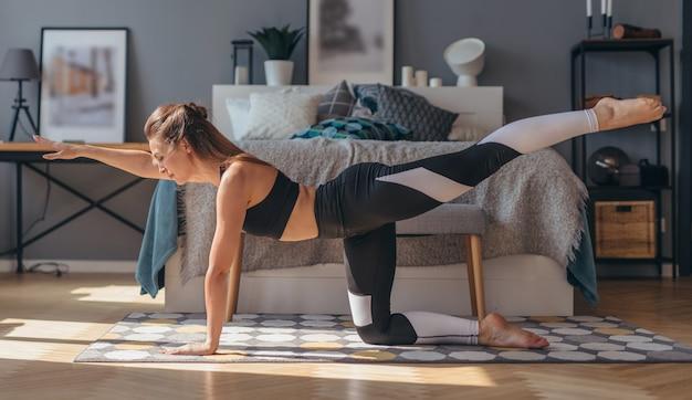 Fitness woman practising yoga doing bird dog exercise.