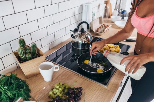 フィットネスの女性がキッチンでオムレツを用意します。フライパンにミルクを注ぐ。