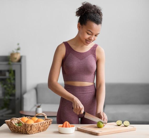 Donna di forma fisica che prepara un succo di frutta