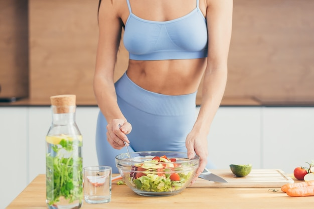 Fitness woman preparing salad at home in the kitchen
