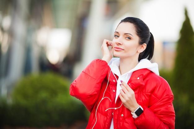 フィットネスの女性。屋外で音楽を実行して聞いているかなりスポーティーな女性。大都会の健康的なライフスタイル。