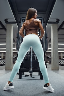 Fitness woman pumping up butt ass booty legs muscles workout fitness and bodybuilding