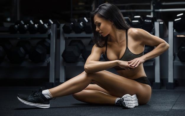 ジムで筋肉トレーニング腹筋、腕、背中、胸部胴体のエクササイズをポンピングするフィットネス女性