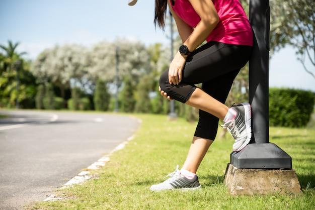 フィットネス女性ランナーは、公園で膝に痛みを感じます。屋外運動のコンセプト。