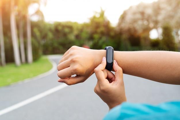 Бегун женщины фитнеса настраивая умные часы перед бежать