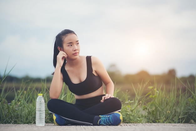 Fitness woman runner sit down relaxing with water bottle after training outside in park