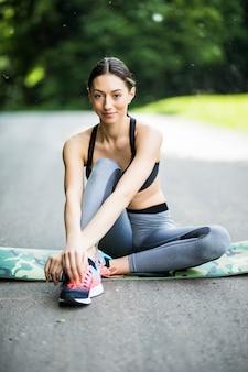 Фитнес женщина-бегун, сидящая после тренировки на улице в парке