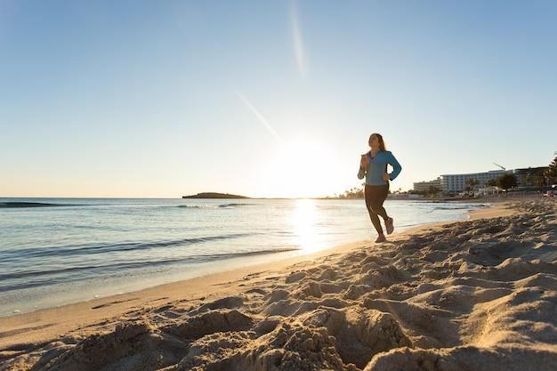 Женщина фитнеса работает на берегу океана на закате.