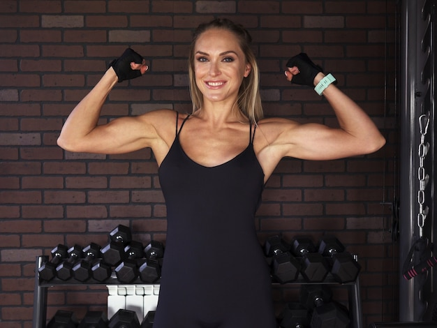Fitness woman showing biceps against brick wall in gym