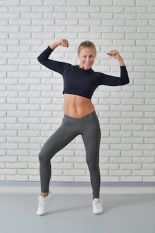 Fitness woman showing the biceps against white brick wall in the gym, full length portrait.