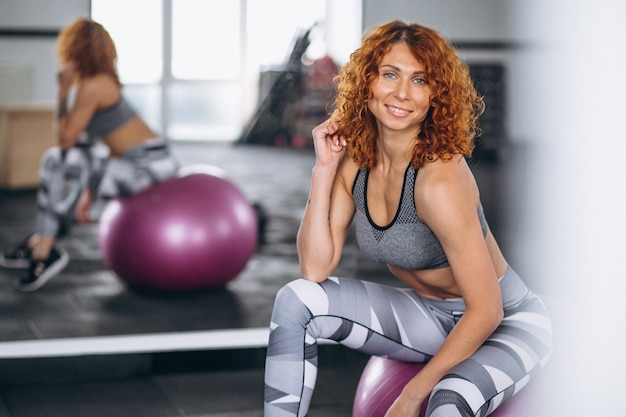 Fitness woman sitting on a fitness ball at the gym