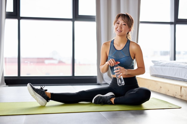 床に座って、水のボトルを持って、トレーニング、運動の後に休むフィットネス女性。明るいスタジオルームで一人でスポーティーなトラックスーツの女性