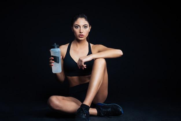 Женщина фитнеса, сидящая на полу с бутылкой воды на черном фоне