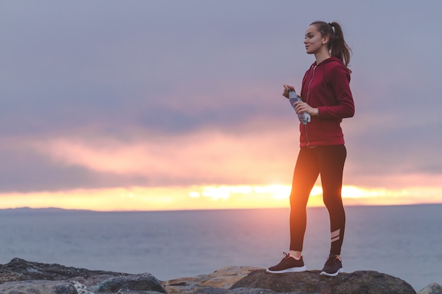 Fitness woman in sneakers standing on a stone, holding a bottle of water and looking into the distance after a workout on a sea background at sunset