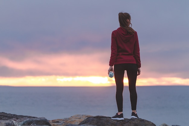 Fitness woman in sneakers standing on a stone, holding a bottle of water and resting after a workout on a sea background at sunset