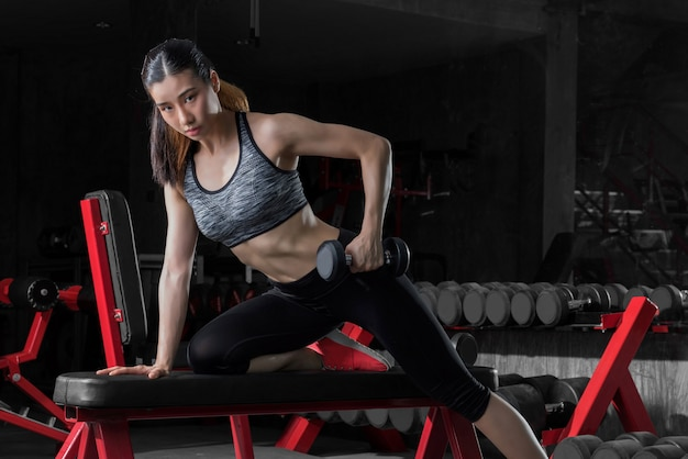 Fitness woman, sporty woman, asian athletic woman pumping up muscles with dumbbells.