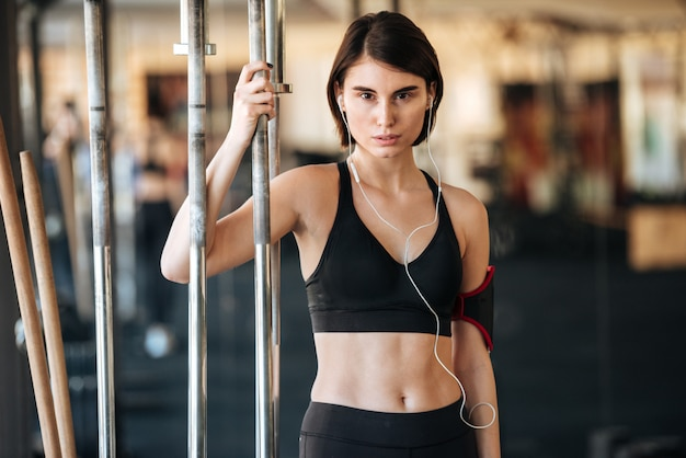 Fitness woman standing and listening to music in gym