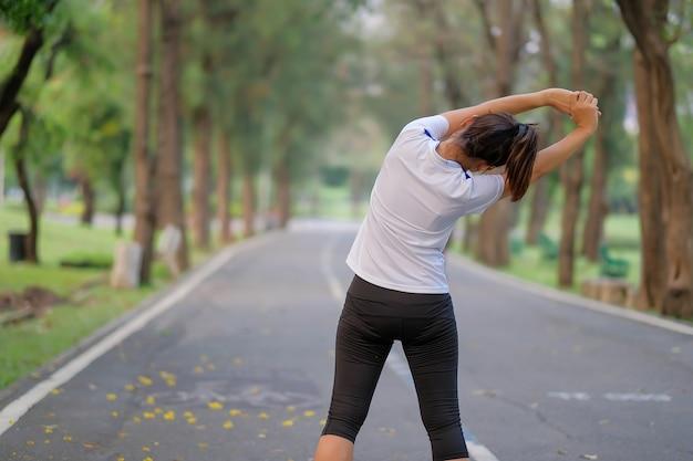 Женщина-фитнес, растягивается в парке, женщина разминка готова для бега трусцой