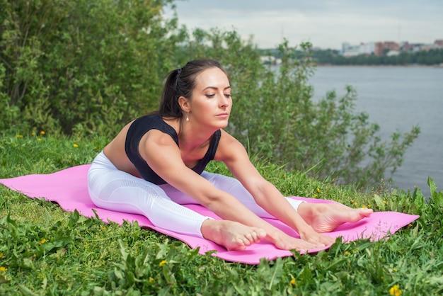 背中を伸ばしてフィットネス女性、ハムストリングの脚の筋肉