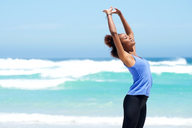 Fitness woman stretching at the beach