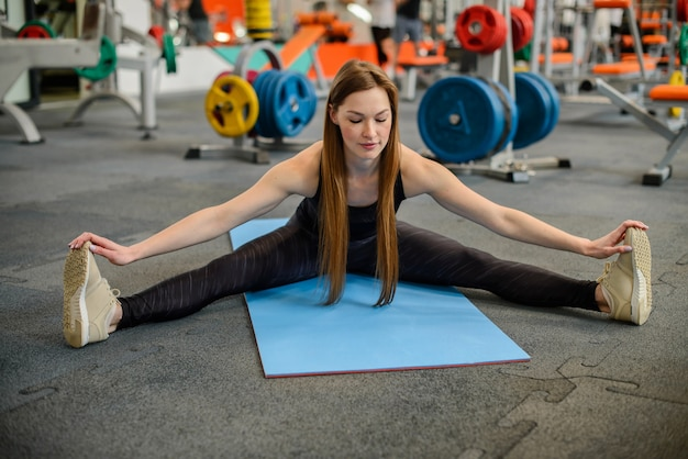 Fitness woman stretching legs sitting on gym mat