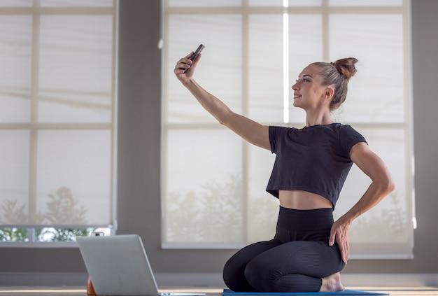 그녀의 컴퓨터로 운동하는 동안 셀카를 찍는 피트니스 여성