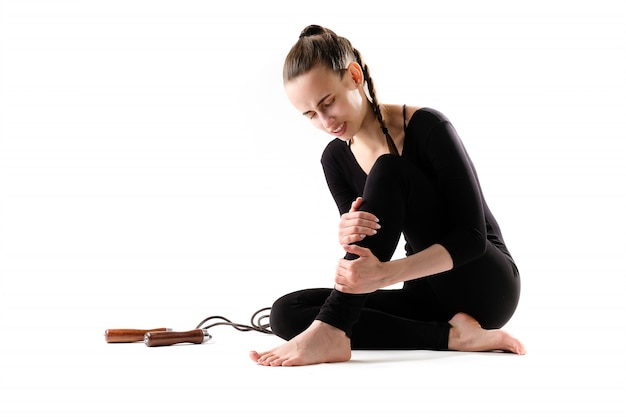Fitness a woman in a tracksuit is in pain due to an injury, holding her leg, next to a jump rope.
