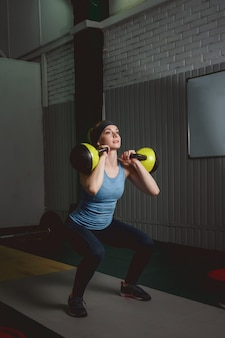 Fitness woman training by kettlebell. fit young lady doing crossfit exercise.