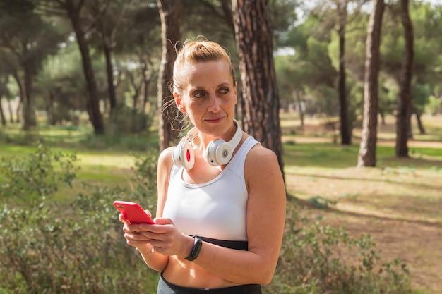 스포츠를 하고 헤드폰으로 음악을 들으며 소셜 미디어에서 스마트폰을 사용하는 피트니스 여성. 건강한 생활.