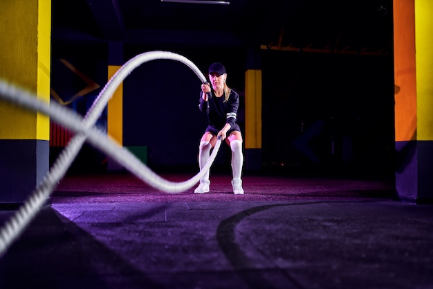 Fitness woman using training ropes for exercise at gym. athlete working out with battle ropes at cross gym