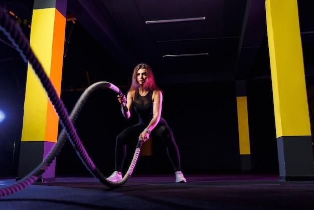 Женщина фитнеса с помощью тренировочных веревок для упражнений в тренажерном зале. спортсмен работает с боевыми канатами в тренажерном зале кросса.