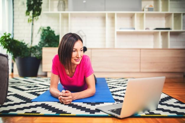 Женщина фитнеса смотрит онлайн-уроки на ноутбуке во время тренировки в гостиной дома.