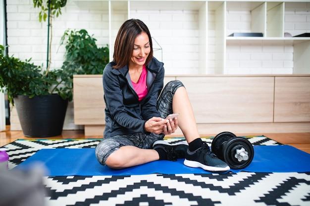 Женщина фитнеса смотрит онлайн-уроки на мобильном телефоне во время тренировки в гостиной дома.