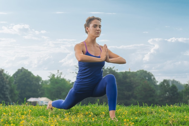 Женщина фитнеса в удобных леггинсах медленно дышит, стоя в позе йоги