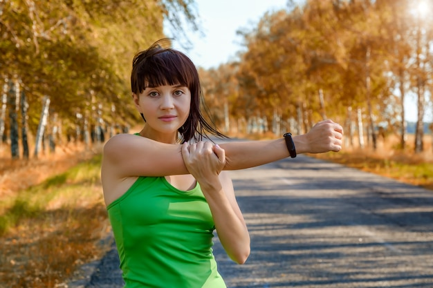 Fitness woman, wearing a smartwatch activity tracker, stretching her arms