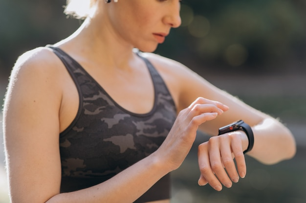 Fitness woman in wireless earphones using smartwatch