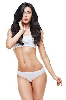 Женщина фитнеса с красивым телом на белом пространстве