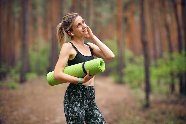 전화를 말하는 공원에서 요가 매트와 함께 피트 니스 여자 또는 무선 헤드폰을 사용하여 음악을들을 수 있습니다.