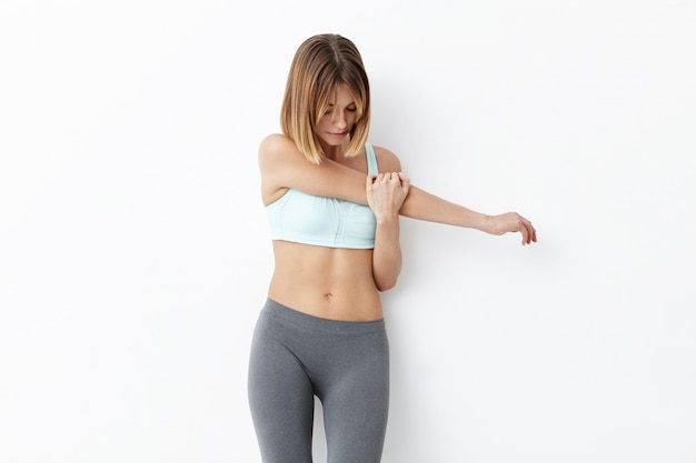 Fitness woman with appealing appearance, stretches hands