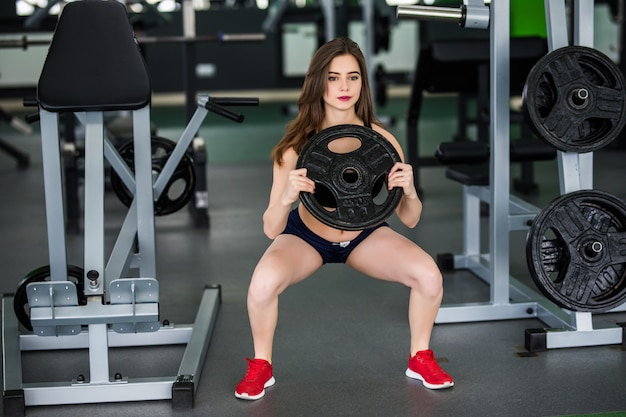 Fitness woman with barbell cargo works in gym alone