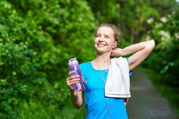 여름 공원에서 훈련을 실행 한 후 병 및 물 수건 피트니스 여자