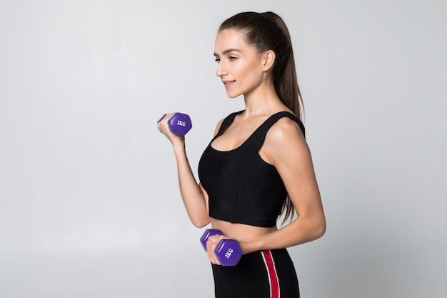 Fitness woman with dumbbell isolated on white wall.