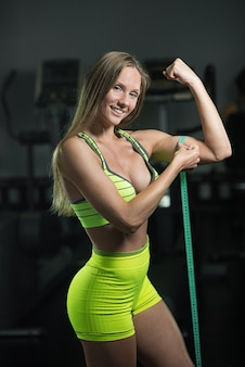 Fitness woman with measure tape measure the circumference of biceps