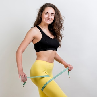 Fitness woman with a measurement tape