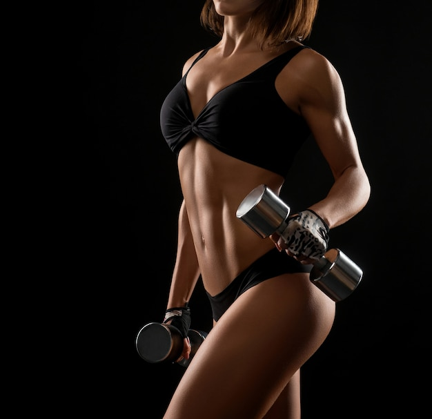 Fitness woman with perfect body holding dumbbells